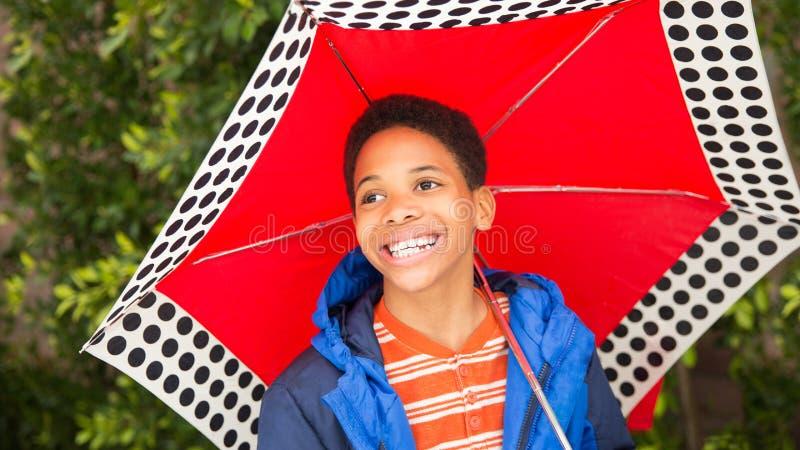 Lyckligt skratta för afrikansk amerikanpojke som rymmer paraplyet arkivbild