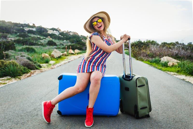 Lyckligt skratta väntande sammanträde för ung kvinna på resväskan på vägen arkivfoto
