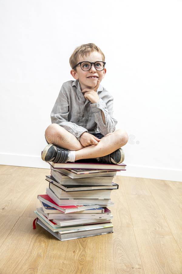 Lyckligt smart barn som överst placeras av böcker som har idé arkivbilder
