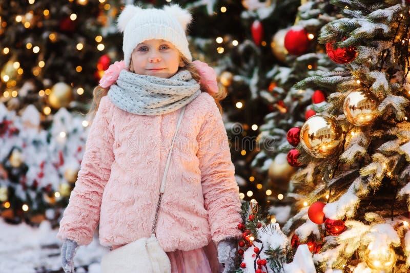 lyckligt spela för barnflicka som är utomhus- på gå i den snöig vinterstaden som dekoreras för nytt år, semestrar royaltyfria bilder
