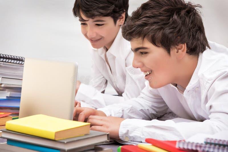 Lyckligt studera för skolpojkar arkivfoton