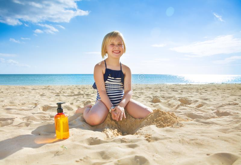 Lyckligt sunt barn i swimwear på att spela för kust arkivfoton