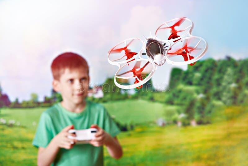 Lyckligt surr för quadcopter för pojkedrevleksak på naturlandskapet royaltyfri bild
