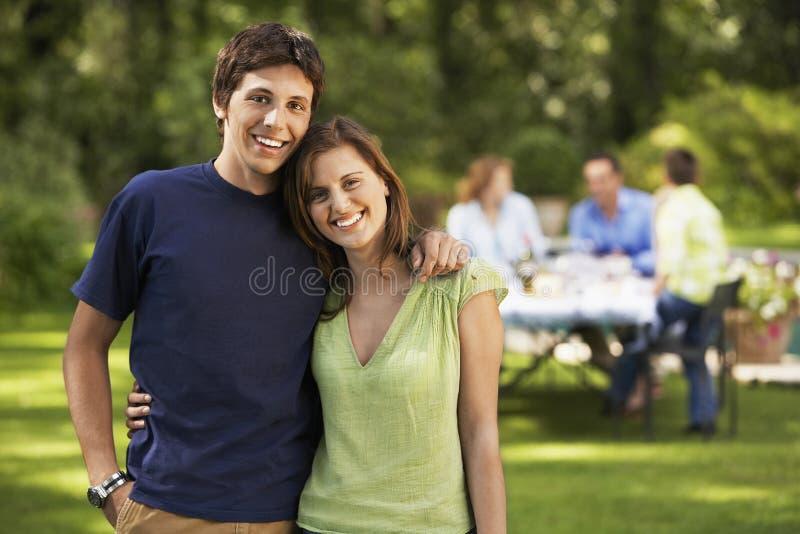 Lyckligt syskon med familjen i trädgård royaltyfri fotografi
