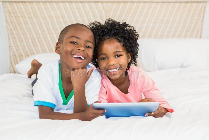 Lyckligt syskon som använder minnestavlan på säng arkivfoto