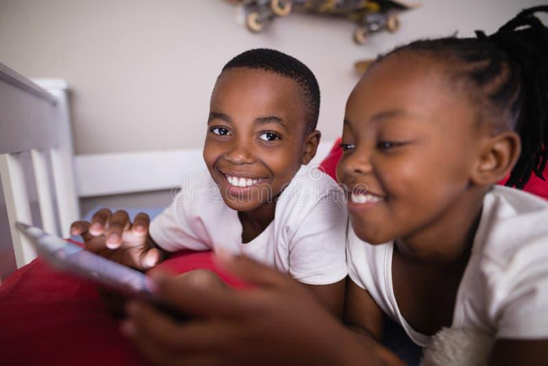 Lyckligt syskon som använder mobiltelefonen, medan ligga på säng hemma royaltyfria bilder
