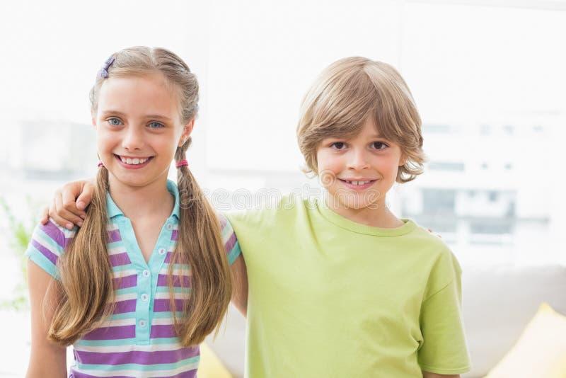 Lyckligt syskon som omkring står armen hemma royaltyfri bild