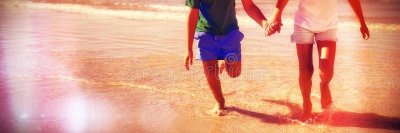 Lyckligt syskon som rymmer händer, medan köra på stranden arkivfoton