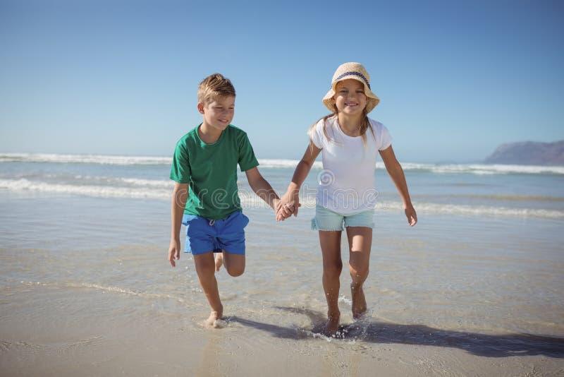 Lyckligt syskon som rymmer händer, medan köra på stranden royaltyfria foton
