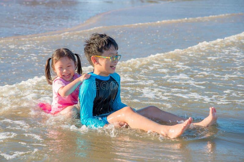 Lyckligt syskon som spelar på stranden arkivfoto