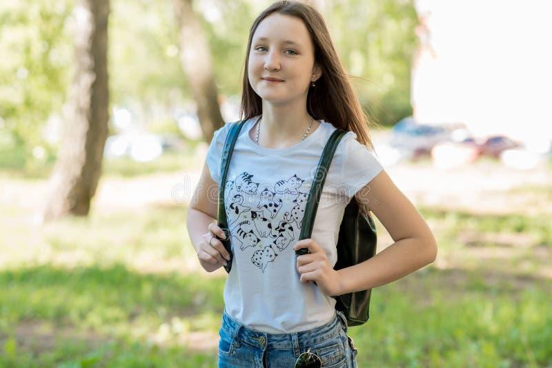 lyckligt teen för flicka Sommar i natur Att le rymmer en ryggsäck bak henne tillbaka Lyckligt se in i ram Hon ler royaltyfri fotografi