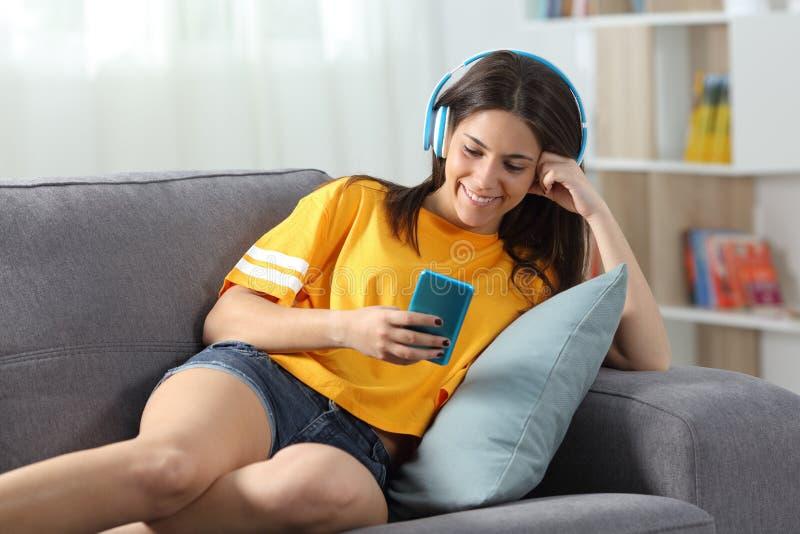 Lyckligt tonårigt lyssna till musik som hemma kontrollerar telefonen på en soffa arkivfoton