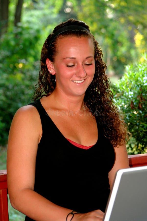 Lyckligt tonårigt se ner på bärbara datorn arkivfoto