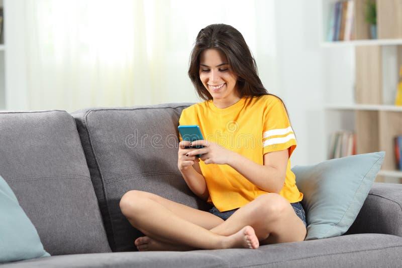 Lyckligt tonårigt smsa på en smartphone på en soffa royaltyfri foto