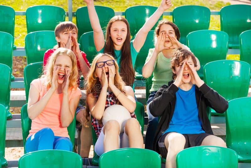 Lyckligt tonåringjubel för laget under leken royaltyfri bild