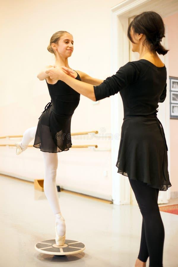 Lyckligt tonårs- ballerinaanseende på tåspetsarna som balanserar på ett jämviktsbräde arkivfoto