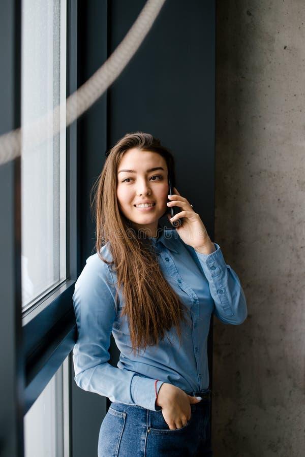 Lyckligt trevligt modellanseende med mobiltelefonen bredvid panoramafönstret royaltyfri foto