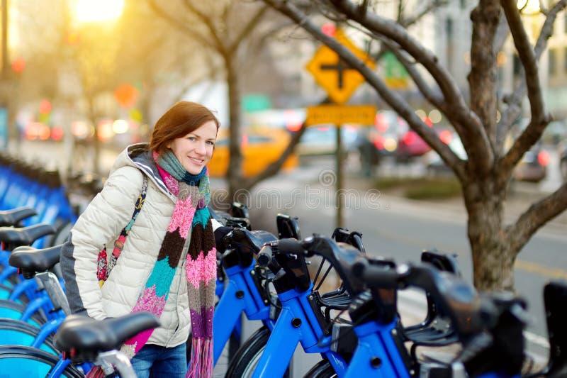 Lyckligt turist- klart för ung kvinna att rida en uthyrnings- cykel i New York City på den soliga vårdagen Kvinnlig handelsresand royaltyfria bilder