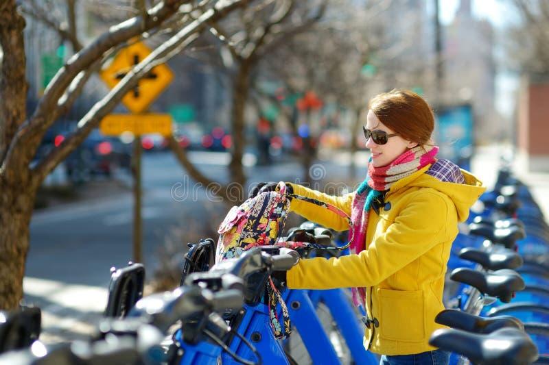Lyckligt turist- klart för ung kvinna att rida en uthyrnings- cykel i New York City på den soliga vårdagen Kvinnlig handelsresand royaltyfri bild