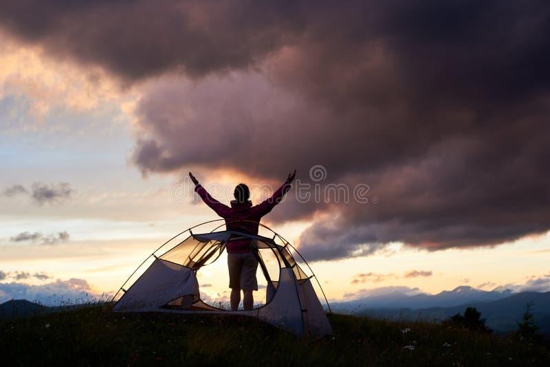 Lyckligt turist- kvinnaanseende nära tältet med lyftta upp händer royaltyfria foton