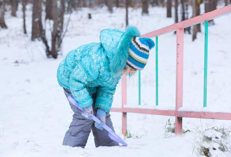 Lyckligt ungeflickabarn utomhus i vintern som gräver snö med leksaksp arkivbild