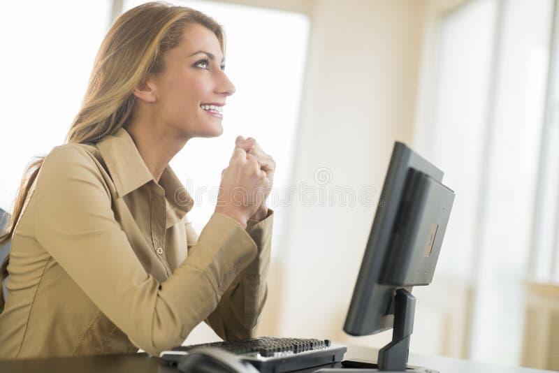 Lyckligt ungt affärskvinnaLooking Up While sammanträde på skrivbordet fotografering för bildbyråer