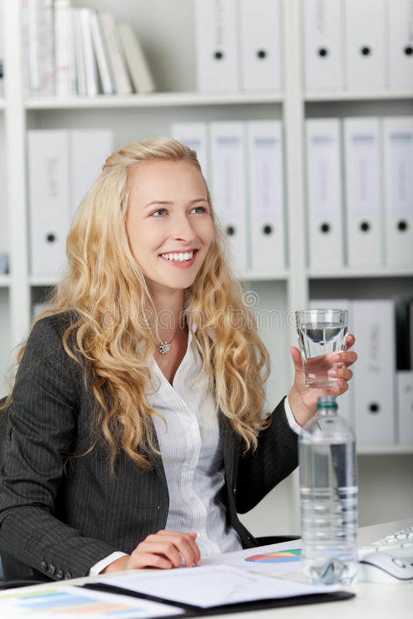 Lyckligt ungt affärskvinnaWith Water In exponeringsglas royaltyfri fotografi