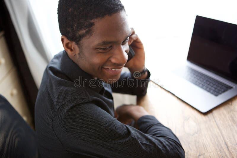 Lyckligt ungt afrikanskt affärsmansammanträde på skrivbordet med datoren och samtal på mobiltelefonen fotografering för bildbyråer