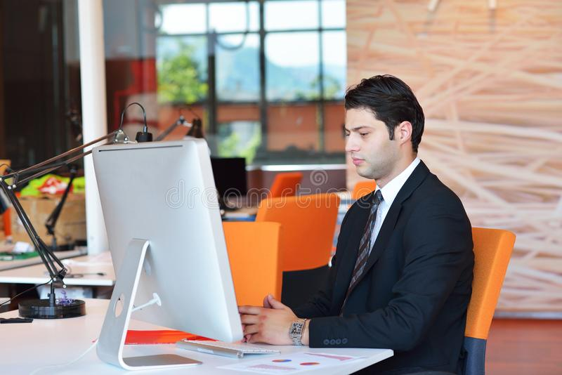 Lyckligt ungt arbete för affärsman i modernt kontor på datoren arkivfoto