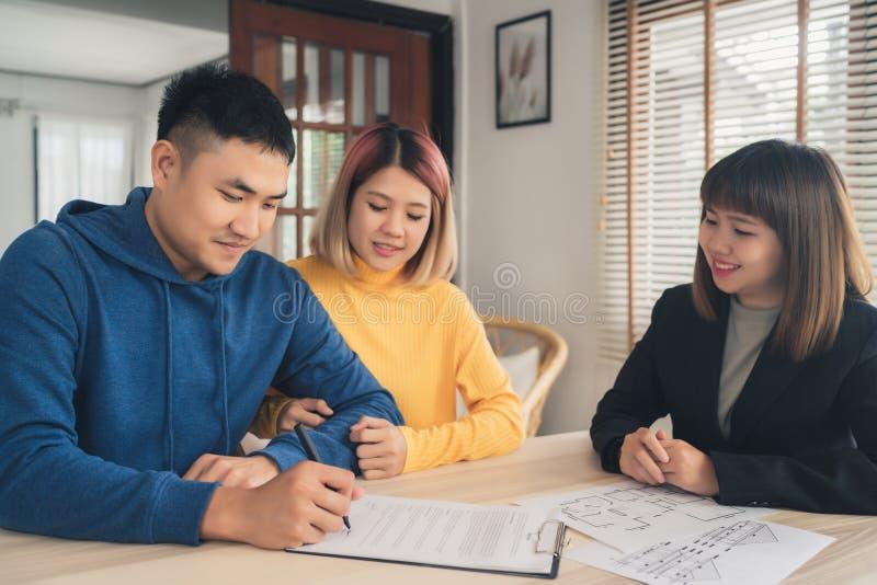 Lyckligt ungt asiatiskt par- och fastighetsmäklaremedel Gladlynt ung man som undertecknar något dokument, medan sitta på skrivbor royaltyfria foton