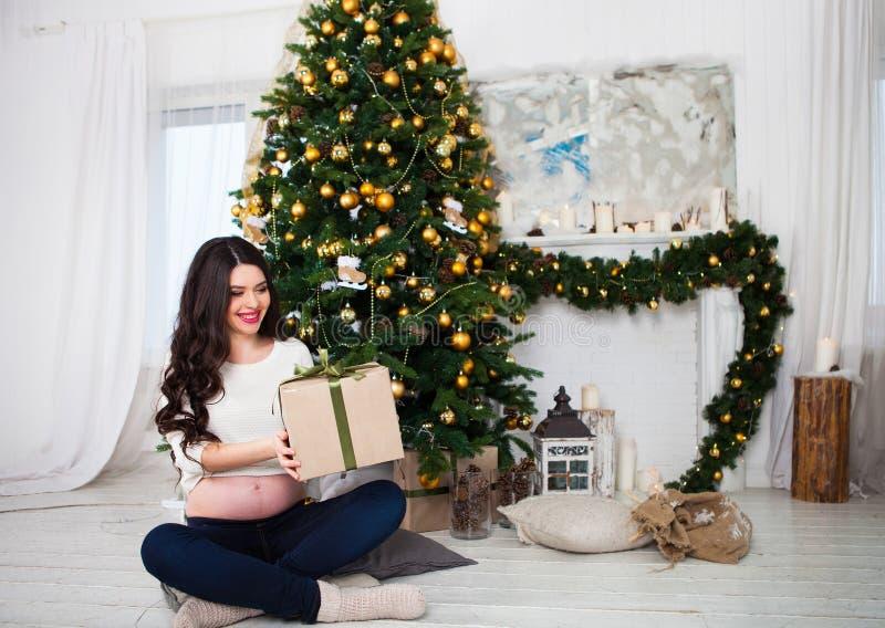 Lyckligt ungt gravid kvinnasammanträde nära julgranen fotografering för bildbyråer