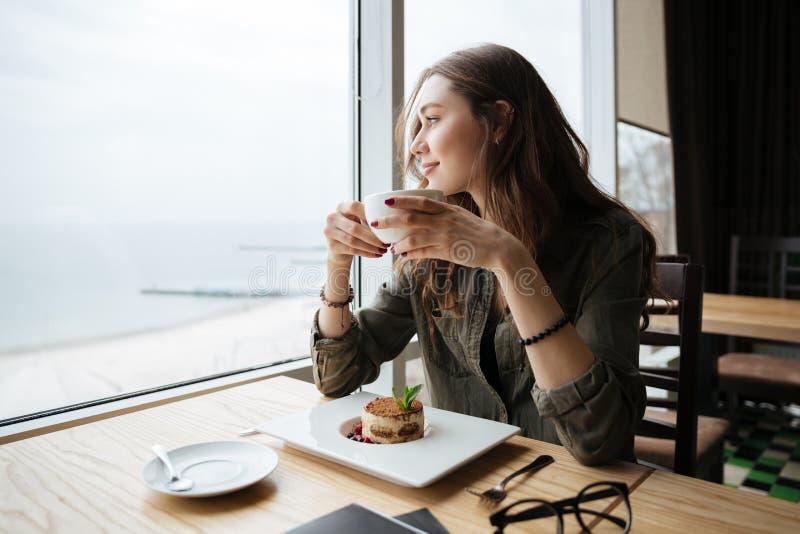 Lyckligt ungt härligt damsammanträde i kafét som dricker kaffe royaltyfri fotografi
