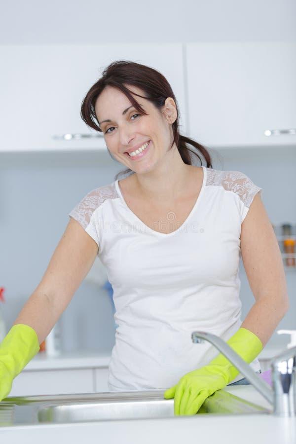 Lyckligt ungt hemmafrulokalvårdmöblemang i kök royaltyfri fotografi