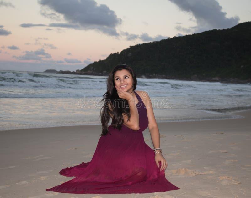 Lyckligt ungt kvinnaplacera och leende på stranden arkivfoton