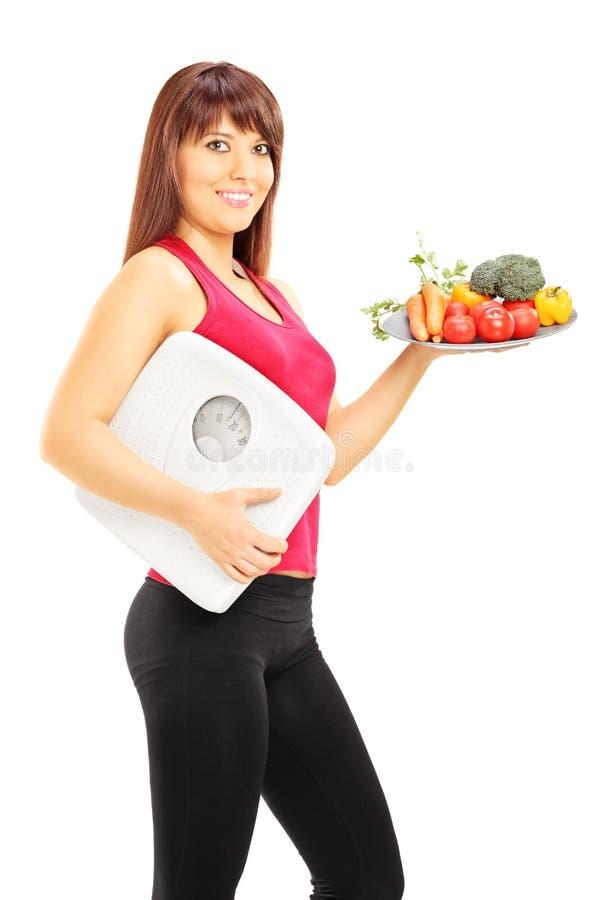 Lyckligt ungt kvinnligt innehav en platta av grönsaker och en viktsc royaltyfri bild
