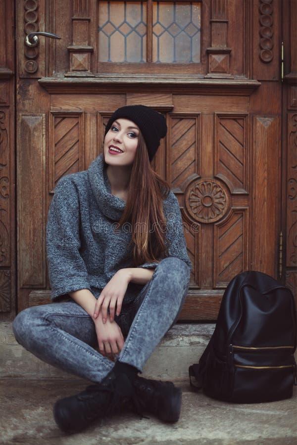 Lyckligt ungt le hipsterkvinnasammanträde nära dörren Gatamodebegrepp tonat royaltyfri fotografi