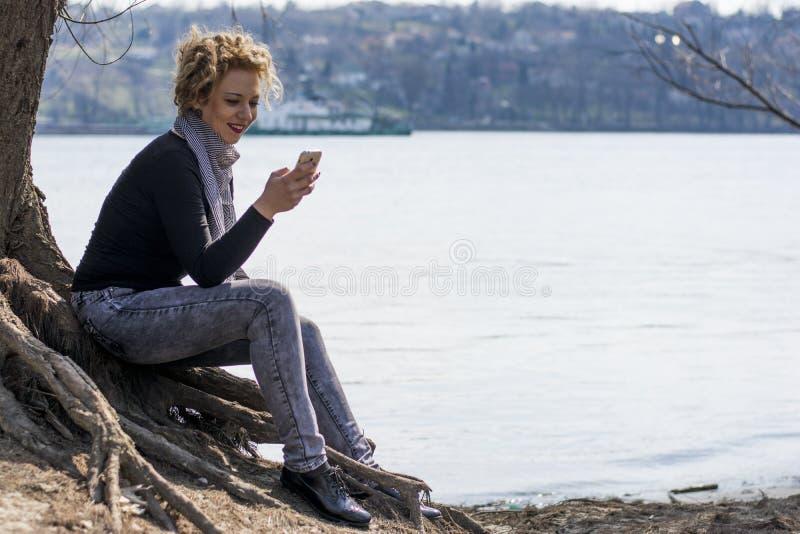 Lyckligt ungt lockigt blont kvinnasammanträde vid floden och maskinskrivningen på royaltyfri foto