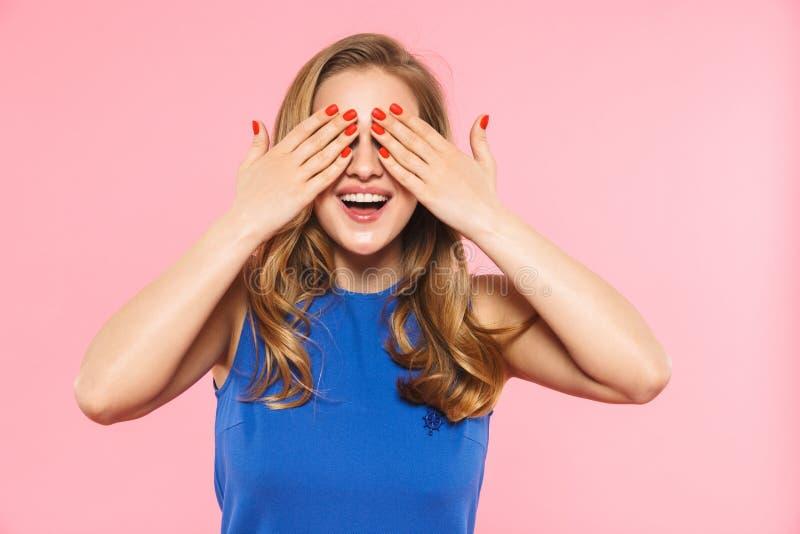Lyckligt ungt nätt posera för kvinna som isoleras över rosa väggbakgrund som täcker ögon arkivbild