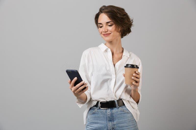 Lyckligt ungt posera för affärskvinna som isoleras över grå väggbakgrund som pratar av mobiltelefonen som dricker kaffe arkivfoton