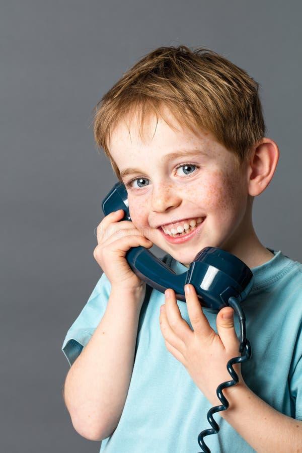 Lyckligt ungt rött hårbarn med fräknar och den gamla telefonen arkivbilder