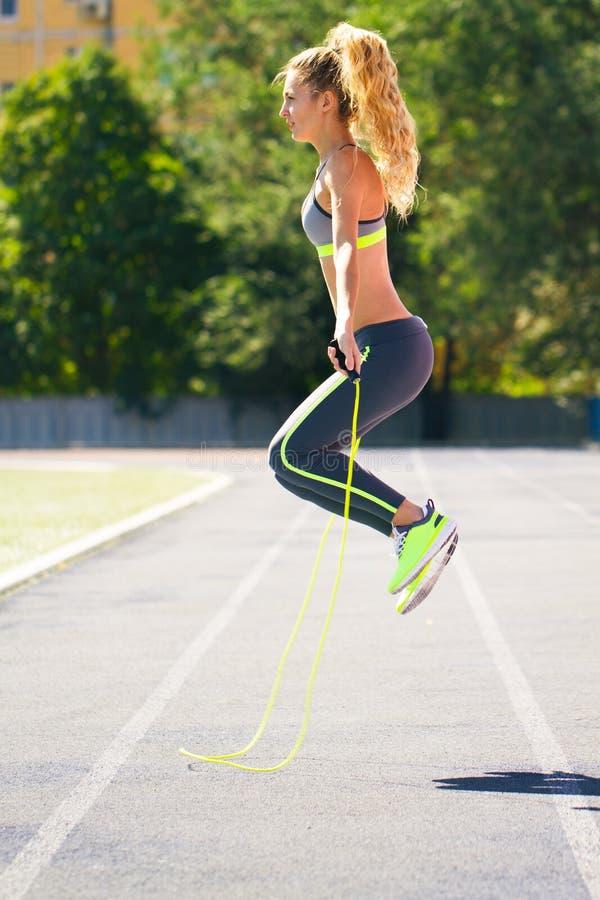 Lyckligt ungt rep för konditionkvinnabanhoppning på stadion royaltyfri fotografi