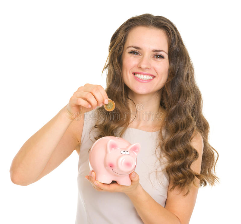 Lyckligt ungt sätta för kvinna myntar in i piggy packar ihop arkivbilder