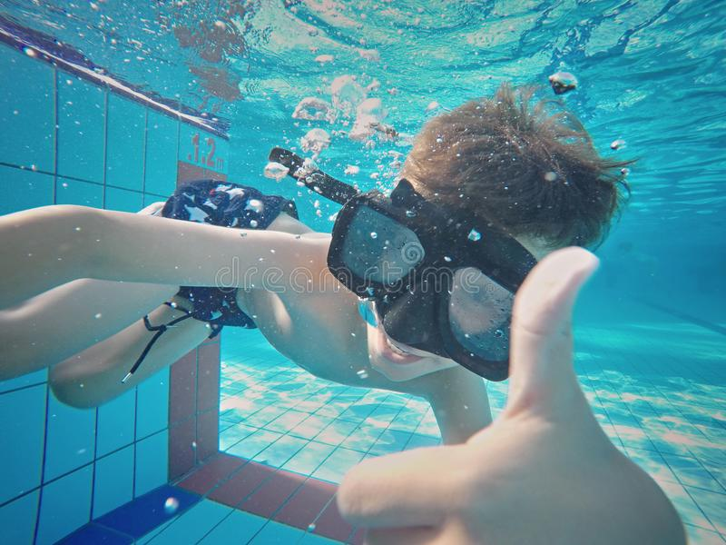 Lyckligt ungt undervattens- pojkebad och dyk, ungebröstslaglängd med gyckel i pöl arkivfoton
