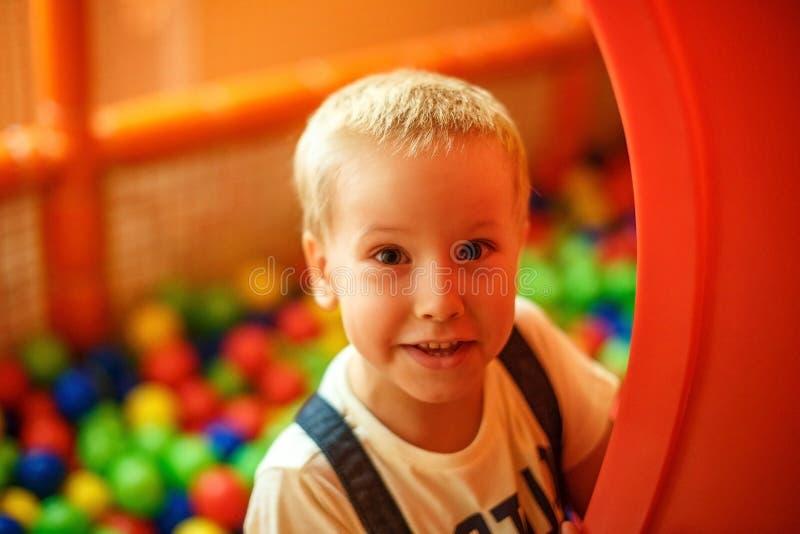 Lyckligt uttryck av framsidan för barn` som s spelar i rummet för barn` s arkivfoton