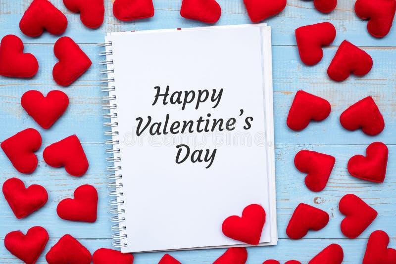 LYCKLIGT VALENTIN DAGord på anteckningsboken med rosa hjärtaformgarnering på blå trätabellbakgrund Gifta sig som är romantiskt oc arkivfoto