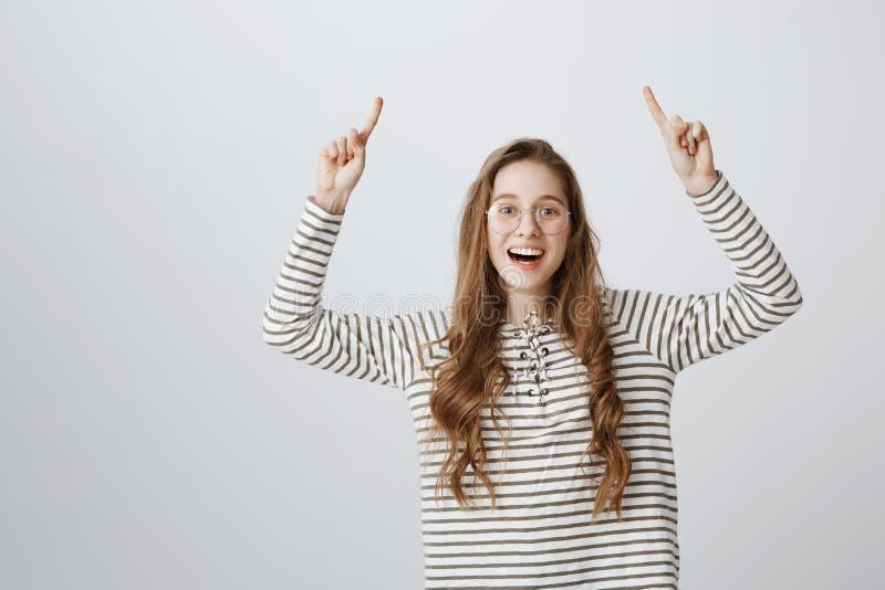 Lyft din hand, om du har idé Studion sköt av den positiva attraktiva unga kvinnan med genomskinliga exponeringsglas som pekar upp arkivbilder