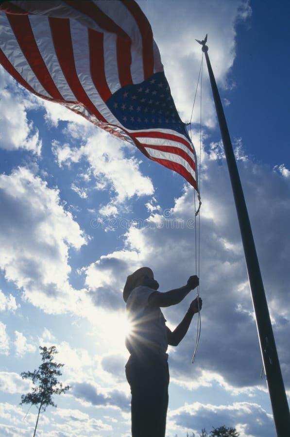 Lyfta amerikanska flaggan fotografering för bildbyråer