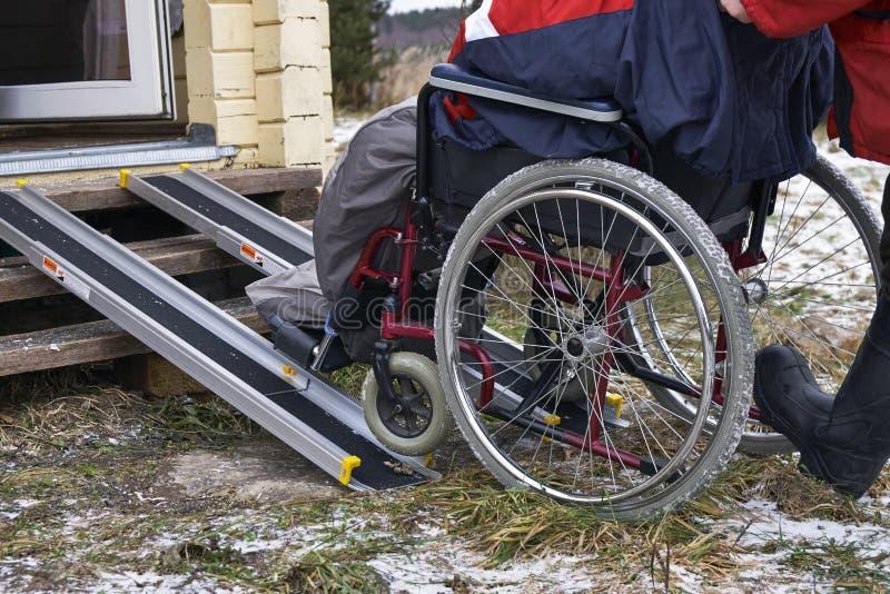 Lyfta ett ogiltigt i en rullstol i ett landshus fotografering för bildbyråer