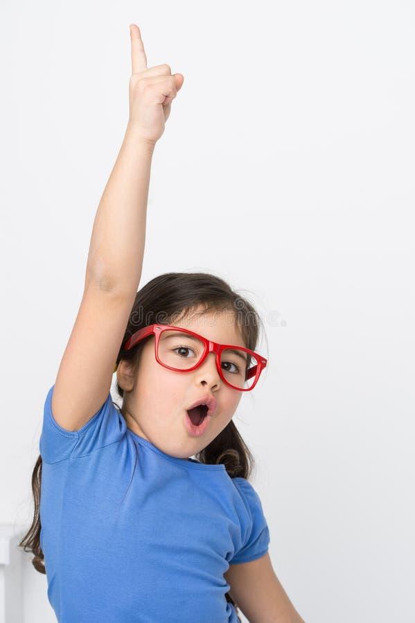 Lyftande hand för rolig liten flicka upp arkivfoto