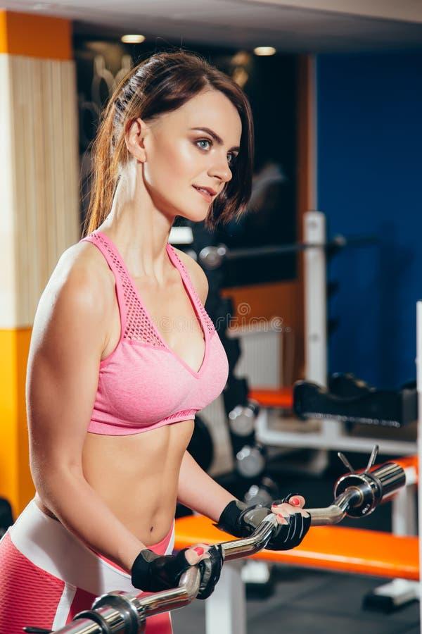 Lyftande skivstång för härlig konditionkvinna Sportkvinnalyftande vikter royaltyfria foton
